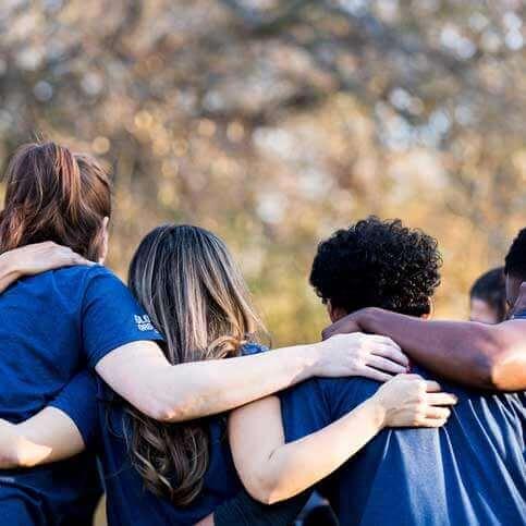 Volunteers hugging in a circle - grant trevithick dallas tx philanthropist